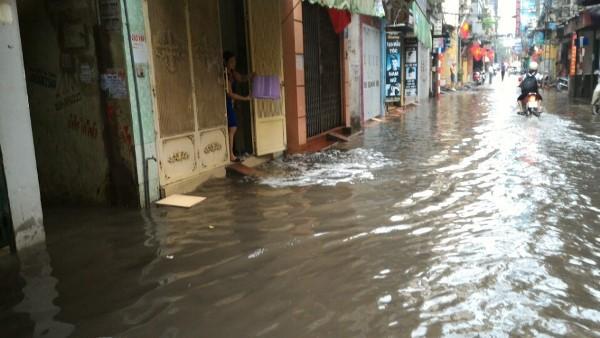 Người dân khu H Tân Mai tát nước từ trong nhà ra ngoài đường