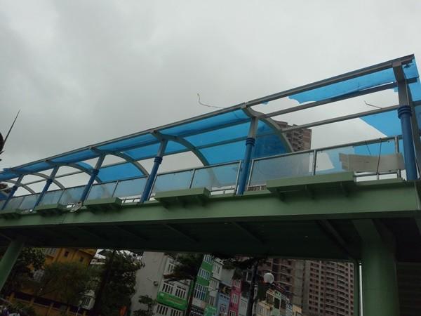 Cầu vượt đi bộ gần trường Tiểu học Tân Mai, đường Tân Mai bị gió lốc bật tung hết tấm phủ nóc bằng nhựa tổng hợp