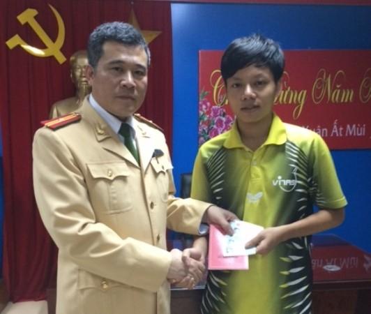 Thiếu tá Nguyễn Văn Hải-Đội phó Đội CSGT số 2 thay mặt BCH đơn vị trao trả lại số tài sản cho anh Đinh Thế Thịnh trong sự mừng vui của anh và gia đình