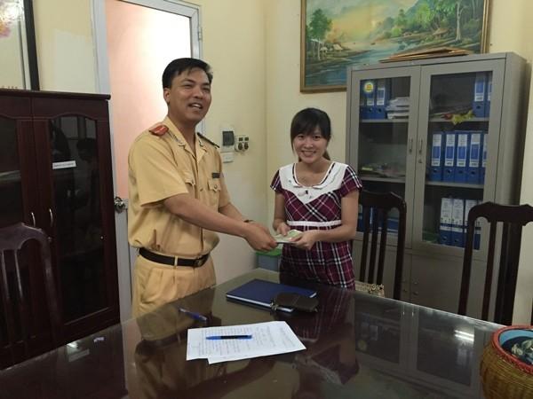 Chị Thu vui mừng, xúc động khi nhận lại số tài sản đánh rơi được Thượng úy Phạm Ngọc Thành-Đội phó Đội CSGT số 7 thay mặt BCH đơn vị trao trả