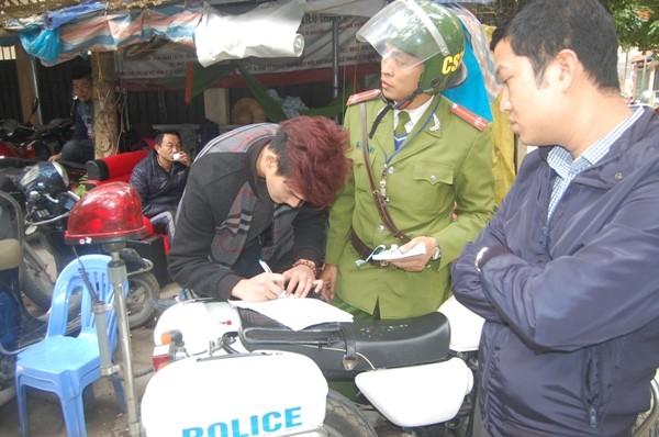 Nhân viên trông giữ xe ký vào biên bản vi phạm