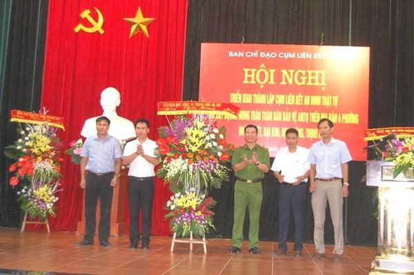 Thiếu tướng Đinh Văn Toản, Phó Giám đốc CATP Hà Nội tặng lẵng hoa chúc mừng các đồng chí Chủ tịch 4 phường trong Cụm liên kết số 2 của quận Hoàng Mai