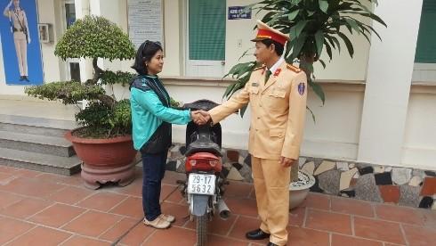 Trung tá Nguyễn Đức Huấn trao trả lại phương tiện cho chị Hằng trong niềm vui mừng khôn xiết của chủ sở hữu