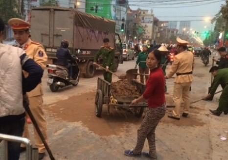 CSGT, CAH Hoài Đức và người dân dọn dẹp số đất cát xe tải làm rơi vãi trên đường để đảm bảo ATGT