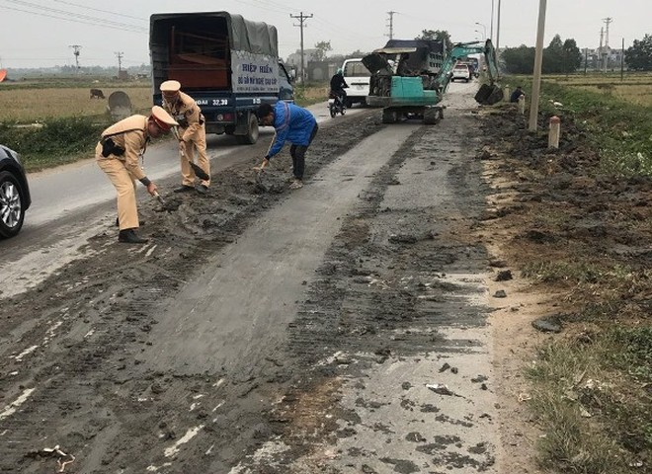 Tổ công tác của Đội CSGT số 10 cùng người dân nhanh chóng dọn dẹp số bùn, đất rơi vãi trên Quốc lộ để đảm bảo ATGT cho người dân và phương tiện