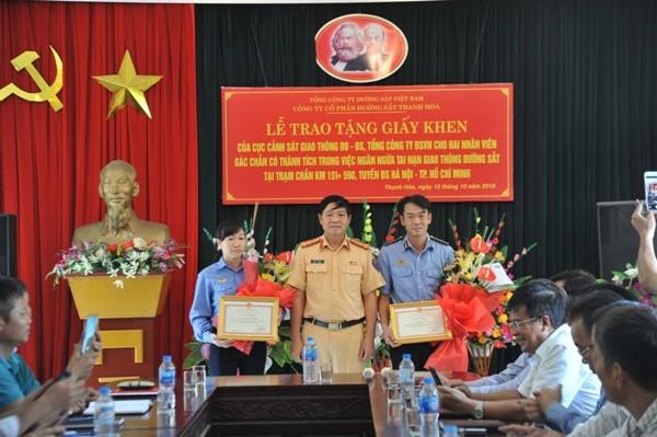Đại diện Cục CSGT khen thưởng cho hai nhân viên gác chắn có thành tích cứu sống nhiều người thoát khỏi tai nạn