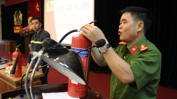 Đại tá Nguyễn Trường Sơn, Phó trưởng Công an quận Cầu Giấy hướng dẫn đội viên bảo vệ, người dân cách thức sử dụng bình chữa cháy