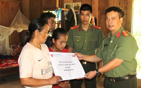 Trung tá Nguyễn Thanh Bình, Tổng Biên tập Báo ANTĐ trao quà của đơn vị và Công ty TNHH Đầu tư Thương mại và Dịch vụ Việt Kiên tới vợ con gia đình đồng chí Thao Văn Súa