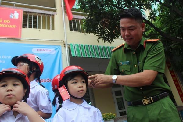 Đại diện CAP Ngọc Hà đội mũ bảo hiểm cho các em học sinh, đồng thời tăng cường các kế hoạch đảm bảo ATGT trên địa bàn