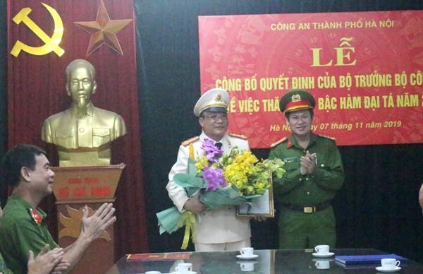 Đại tá Nguyễn Văn Viện, Phó Giám đốc CATP Hà Nội thừa ủy quyền của lãnh đạo Bộ Công an trao quyết định thăng cấp bậc hàm Đại tá cho đồng chí Nguyễn Tiến Tần