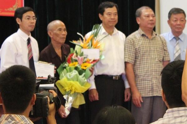 Ông Trần Văn Thêm (ôm hoa) tại buổi xin lỗi công khai, sáng 11-8