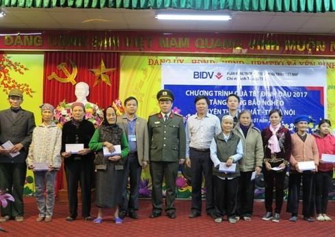 Đại diện Báo An ninh Thủ đô và Ngân hàng BIDV Thạch Thất chụp ảnh lưu niệm với một số hộ dân nghèo tại xã Yên Bình và Yên Trung