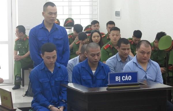 Trần Anh Quang (hàng trên, ngoài cùng, bên phải) và đồng phạm tại phiên tòa.