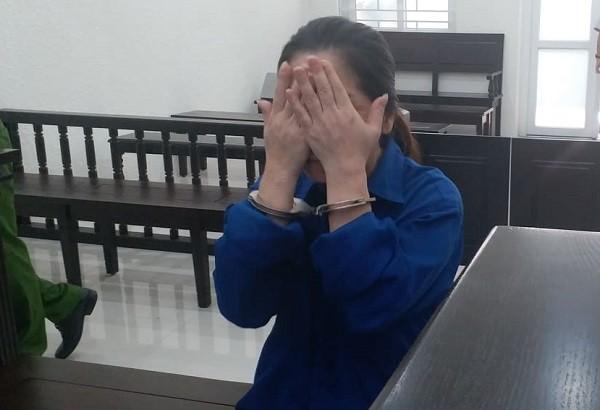 Bị cáo Chử Thị Minh Thu luôn đưa tay che mặt khi bị chụp hình.