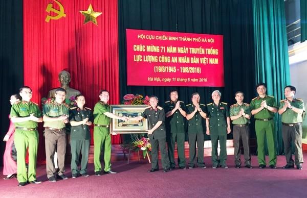 Đại diện Đảng ủy, Ban giám đốc CATP Hà Nội trao tặng Hội Cựu chiến binh TP Hà Nội món quà lưu niệm tại buổi giao lưu gặp mặt