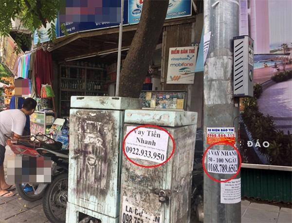 Một số tờ rơi có nội dung cho vay tài chính dán tại các cột đèn, bốt điện tại địa bàn phường Giảng Võ, quận Ba Đình