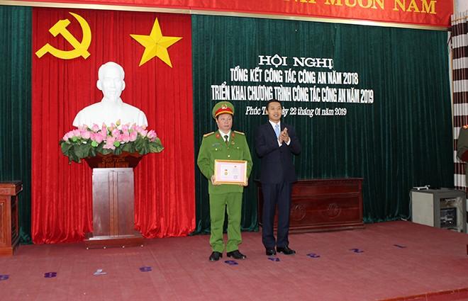 Đồng chí Doãn Trung Tuấn, Phó Bí thư, Chủ tịch UBND huyện Phúc Thọ trao tặng Kỷ niệm chương cho Đại tá Bùi Xuân Trường, Trưởng CAH Phúc Thọ