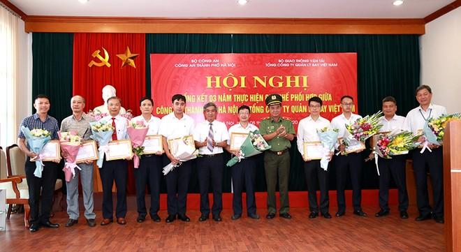 Thiếu tướng Nguyễn Anh Tuấn và ông Lê Quốc Khánh tặng Giấy khen và hoa của Giám đốc CATP Hà Nội cho tập thể, cá nhân thuộc TCT QLB VN có thành tích xuất sắc trong thực hiện quy chế phối hợp