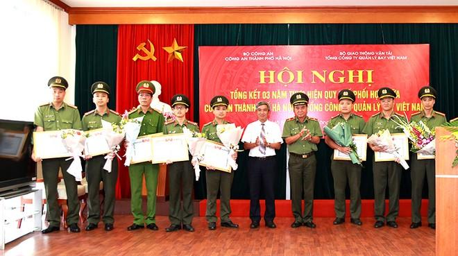 Ông Lê Quốc Khánh và Thiếu tướng Nguyễn Anh Tuấn tặng Giấy khen và hoa của TCT QLB Việt Nam cho tập thể, cá nhân thuộc CATP Hà Nội có thành tích xuất sắc trong thực hiện quy chế phối hợp