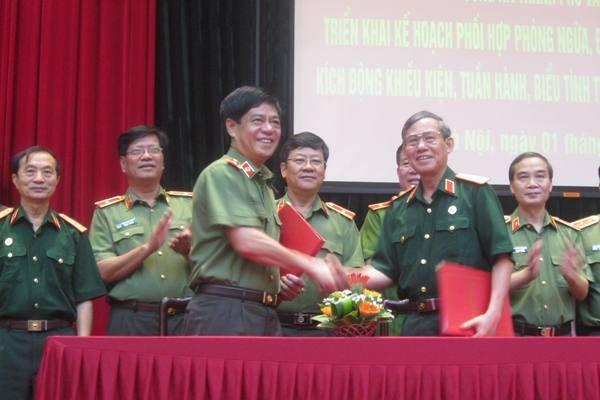 Thiếu tướng Đoàn Duy Khương và Trung tướng Lê Minh Cường trao văn bản ký kết Chương trình phối hợp trong những năm tiếp theo.