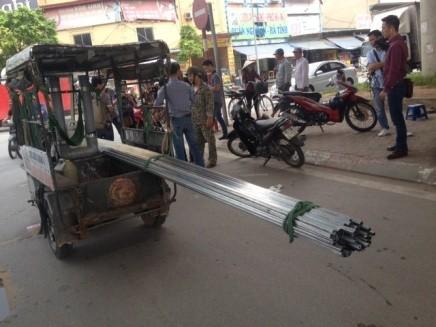 Những chiếc xe ba bánh tự chế chở những cây sắt, thép dài như những mũi giáo khổng lồ