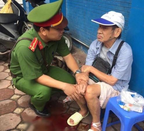 Thượng úy Nguyễn Bá Huy kiên nhẫn động viên cụ ông bị thương ở chân (ảnh Facebook)