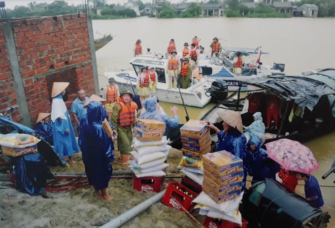 Các chiến sỹ Công an trao tận tay bà con vùng ngập lụt những thùng mì tôm, bao gạo