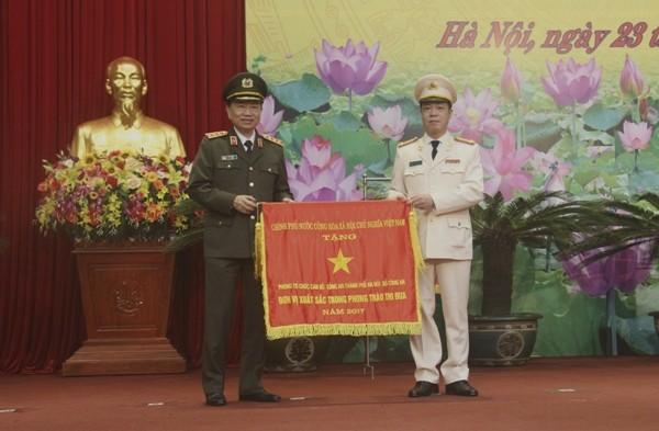 Thừa ủy quyền của Thủ tướng Chính phủ, đồng chí Bộ trưởng Tô Lâm trao Cờ thi đua của Chính phủ tặng Phòng Tổ chức cán bộ