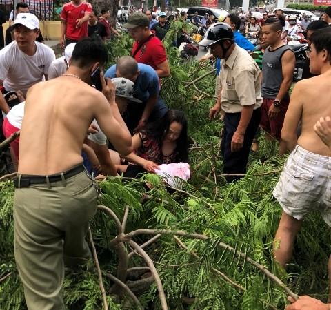 Người phụ nữ đau đớn ôm nam thanh niên đi cùng mình bị cành cây đâm trúng vùng mặt