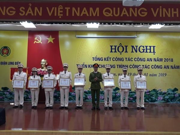 Trung tá Tô Anh Dũng - Trưởng CAQ Long Biên trao quyết định khen thưởng cho các tập thể, cá nhân lập thành tích xuất sắc