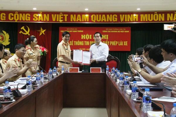 Trung tướng Vũ Đỗ Anh Dũng và ông Nguyễn Văn Huyện bàn giao thông tin truy cập phần mềm