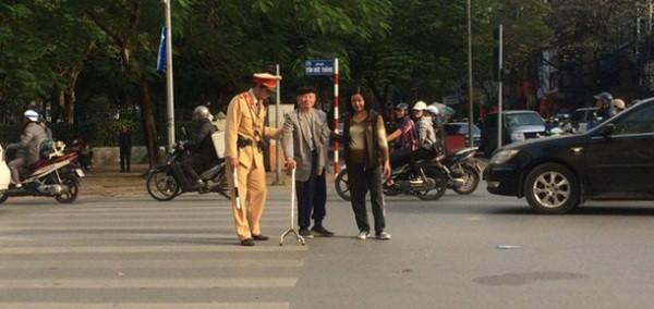 Chiến sỹ CSGT dắt người già qua đường (ảnh: Phương Thảo)