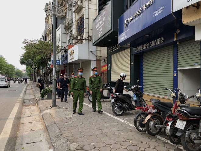 """Tổ công tác CAP Kim Mã, quận Ba Đình tuần tra giám sát và nhắc nhở các hộ kinh doanh tạm thời ngừng hoạt động để chống """"giặc"""" Covid-19"""