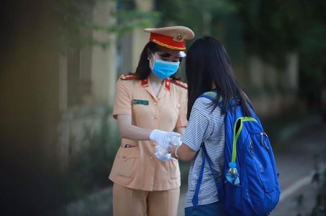 Chiến sỹ CSGT CATP Hà Nội phát khẩu trang, nước uống cho thí sinh dự kỳ thi THPT