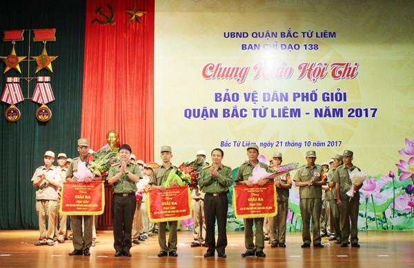 Thượng tá Nguyễn Đăng Vinh, Phó trưởng Phòng Công tác Chính trị và Thượng tá Nguyễn Văn Phong, Phó trưởng Phòng Xây dựng phong trào toàn dân bảo vệ ANTQ trao giải 3 cho 3 đội thi của các phường Cổ Nhuế 2, Phúc Diễn, Phú Diễn