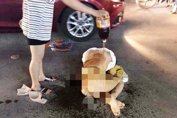 Cô gái bị lột trần, cả áo lót cũng bị vứt ra bên cạnh và bị người phụ nữ đổ chất lỏng nghi là nước mắm lên người