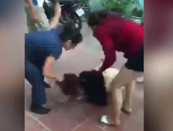 """Mẹ chồng (người phụ nữ mặc áo đen) đánh tới tập vào mặt người phụ nữ bị coi là có quan hệ """"ngoài luồng"""" với con trai (Ảnh cắt từ clip)"""