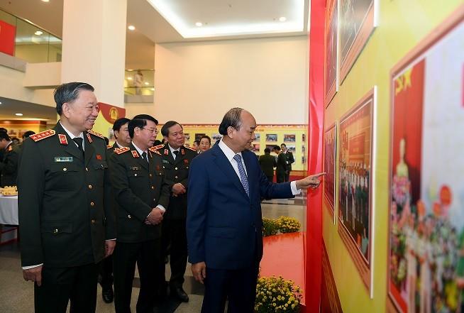 Thủ tướng Nguyễn Xuân Phúc và các đồng chí lãnh đạo Bộ Công an xem triển lãm hình ảnh về hoạt động của lực lượng CAND được trưng bày trong khuôn khổ Hội nghị