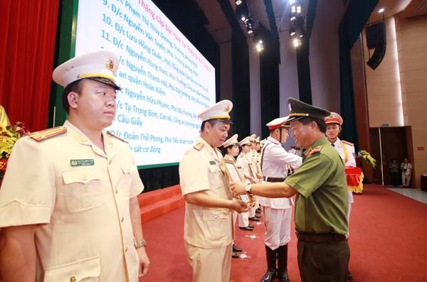 Thiếu tướng Đoàn Ngọc Hùng, Phó Giám đốc CATP Hà Nội trao quyết định thăng cấp bậc hàm từ Thiếu tá lên Trung tá cho các cá nhân