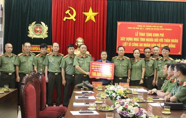 Đại diện các đơn vị trong Cụm thi đua số 4 CATP Hà Nội tặng số tiền 100 triệu đồng do CBCS trong Cụm quyên góp xây dựng nhà tình nghĩa cho thân nhân liệt sỹ
