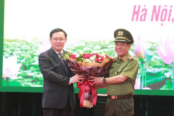 Đồng chí Vương Đình Huệ, Ủy viên Bộ Chính trị, Bí thư Thành ủy Hà Nội tặng hoa chúc mừng Trung tướng Đoàn Duy Khương hoàn thành nhiệm vụ