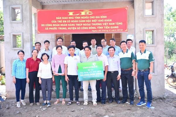 Gia đình ông Huỳnh Văn Được cùng đại diện Vietcombank và lãnh đạo địa phương chụp ảnh lưu niệm bên ngôi nhà mới