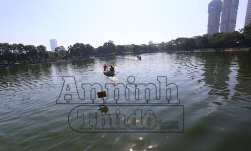 Công nhân rải chế phẩm Redoxy 3C tại hồ Nghĩa Tân, quận Cầu Giấy, Hà Nội
