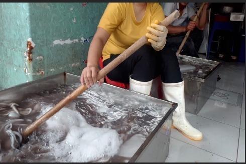 Công nhân tại cơ sở ngâm bạch tuộc trong chậu inox chứa dung dịch
