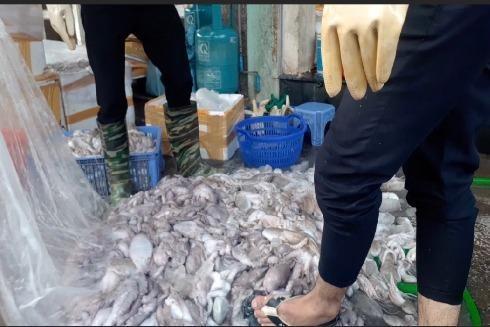 Công nhân của cơ sở dùng chân để gạt bạch tuộc trên vỉa hè