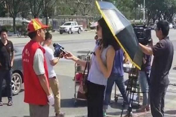 Hình ảnh phóng viên cầm ô khi phỏng vấn tình nguyện viên ở Hạ Môn