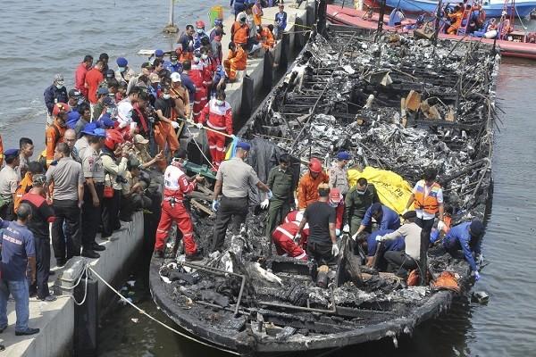 Các nhân viên cứu hộ tìm kiếm các nạn nhân vụ cháy phà