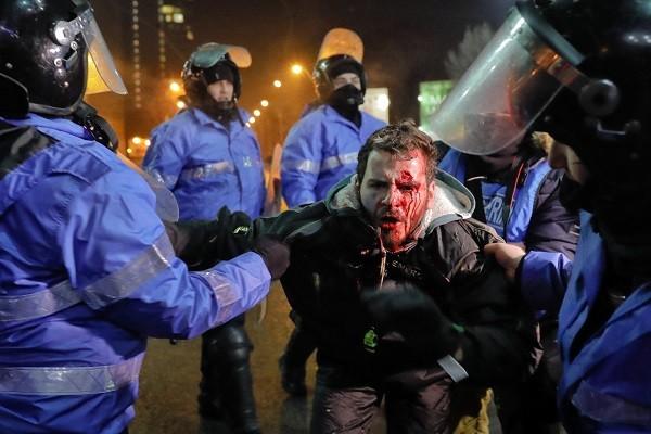 Cảnh sát chống bạo động bắt giữ một người biểu tình