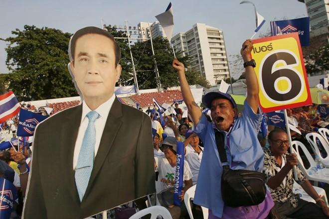 Những người ủng hộ đảng Palang Pracharat cầm poster in hình ông Prayut