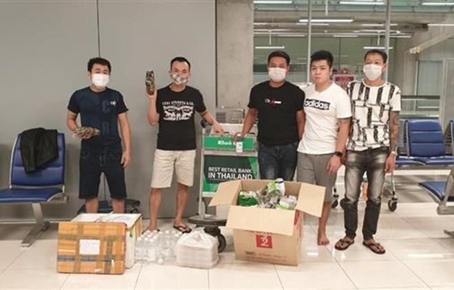 Nhóm công dân Việt Nam bị mắc kẹt tại sân bay Survanabhumi tiếp nhận thức ăn và đồ dùng thiết yếu do cán bộ Đại sứ quán chuyển đến. (Ảnh: TTXVN)